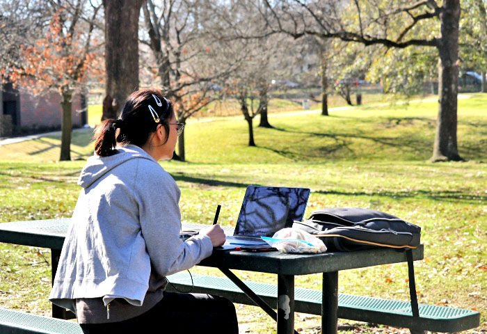 Student does school work as she enjoys weather
