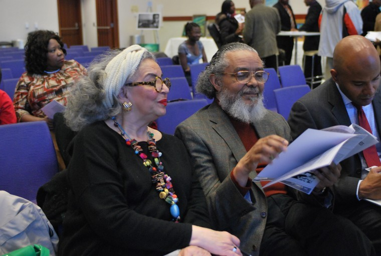 Doctor Peniel Joseph (right), Representative Byron Rushing (middle) and his wife (left) looking over a flyer for the event.