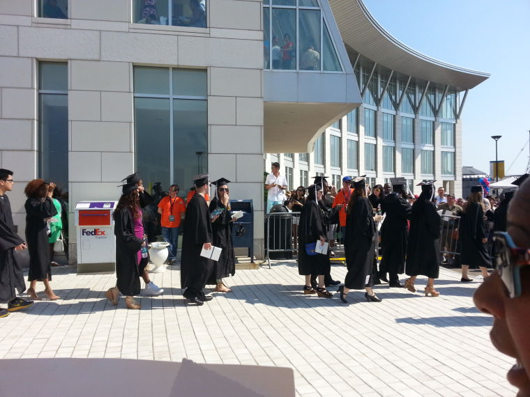 Graduates walk down the steps to the Campus Center.