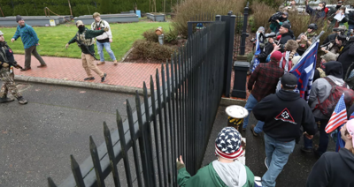 Supporters of President Donald Trump breach a perimeter fence outside the Governor's Mansion