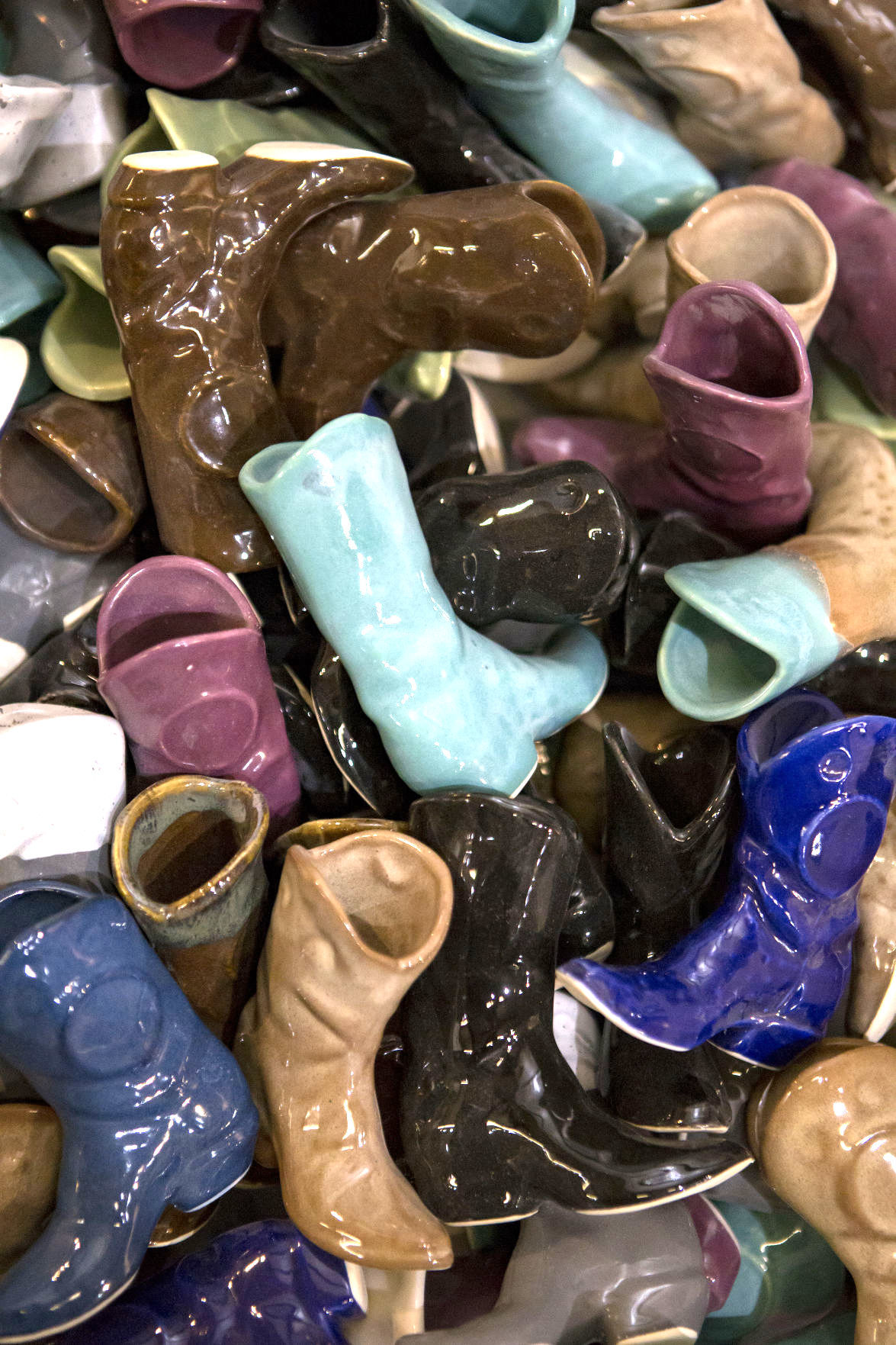 Ceramic cowboy boots sit in a bin for sale at Clay in Motion.