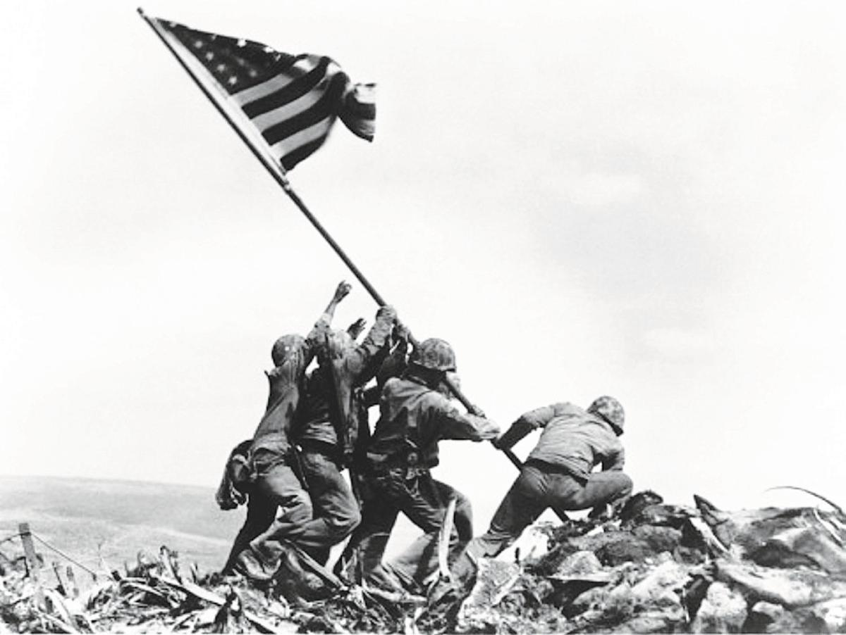 Marines raise the flag atop Mount Suribachi