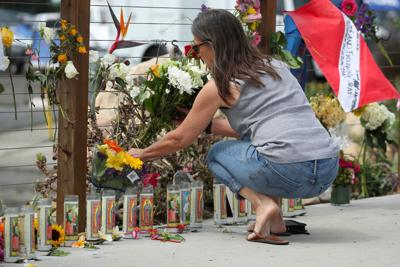 A woman places flowers at a makeshift memorial