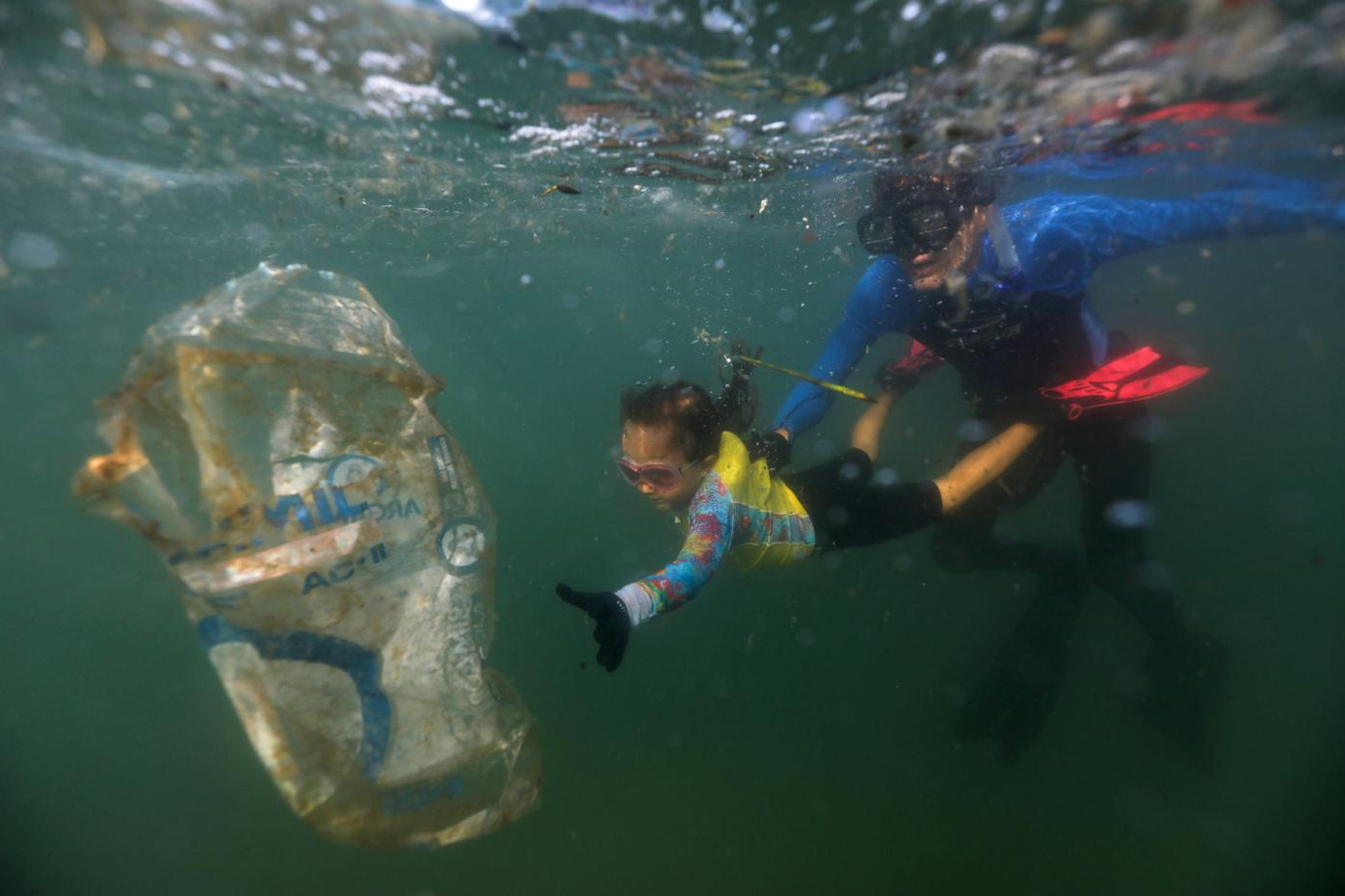 """Nina Gomes, who was named as the youngest """"Green Agent"""" by the Municipal Urban Cleaning Company, collects garbage in the sea in Rio de Janeiro"""