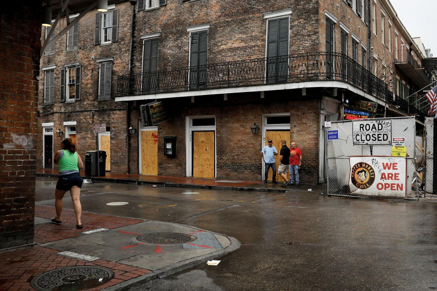 People walk past boarded up windows in Bourbon Street at the French Quarter ahead of Hurricane Ida, in New Orleans
