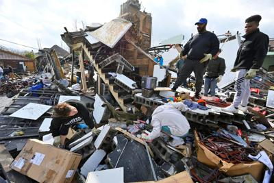 People try to salvage merchandise at Music City Vintage after a tornado hit eastern Nashville