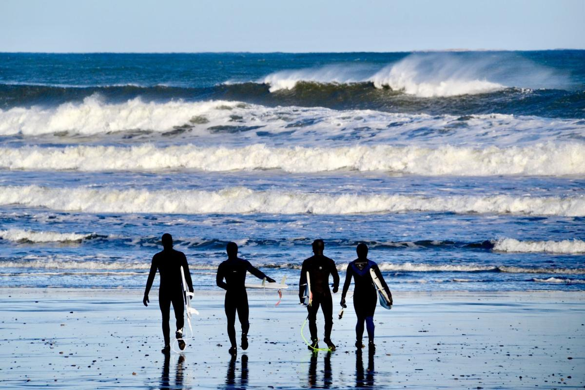 Surfers head out to the water