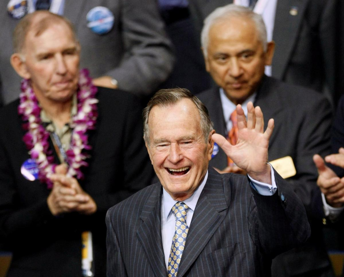 FILE PHOTO: Former U.S. President George H.W. Bush waves as he enters the second session of the 2008 Republican National Convention in St. Paul, Minnesota