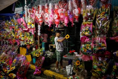 A vendor arranges a flower bouquet a day before Valentines Day in Dangwa Flower Market in Manila