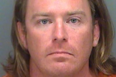 Adam Christian Johnson, who was arrested on a federal warrant, poses in a Pinellas County jail booking photograph