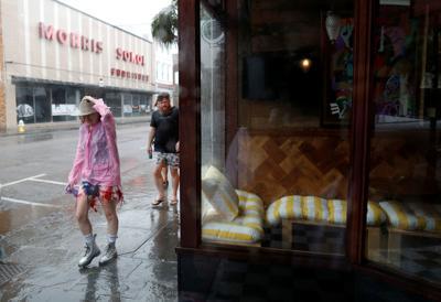 People navigate the wind and rain along King Street during Hurricane Dorian in Charleston