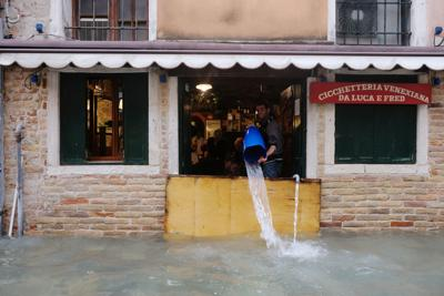 A man removes water from the flooded shop during a period of seasonal high water in Venice
