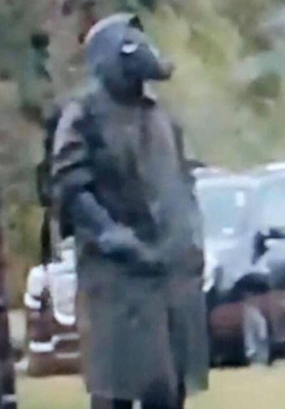 Creepy figure in trench coat, gas mask behind Exeter school raises alarm