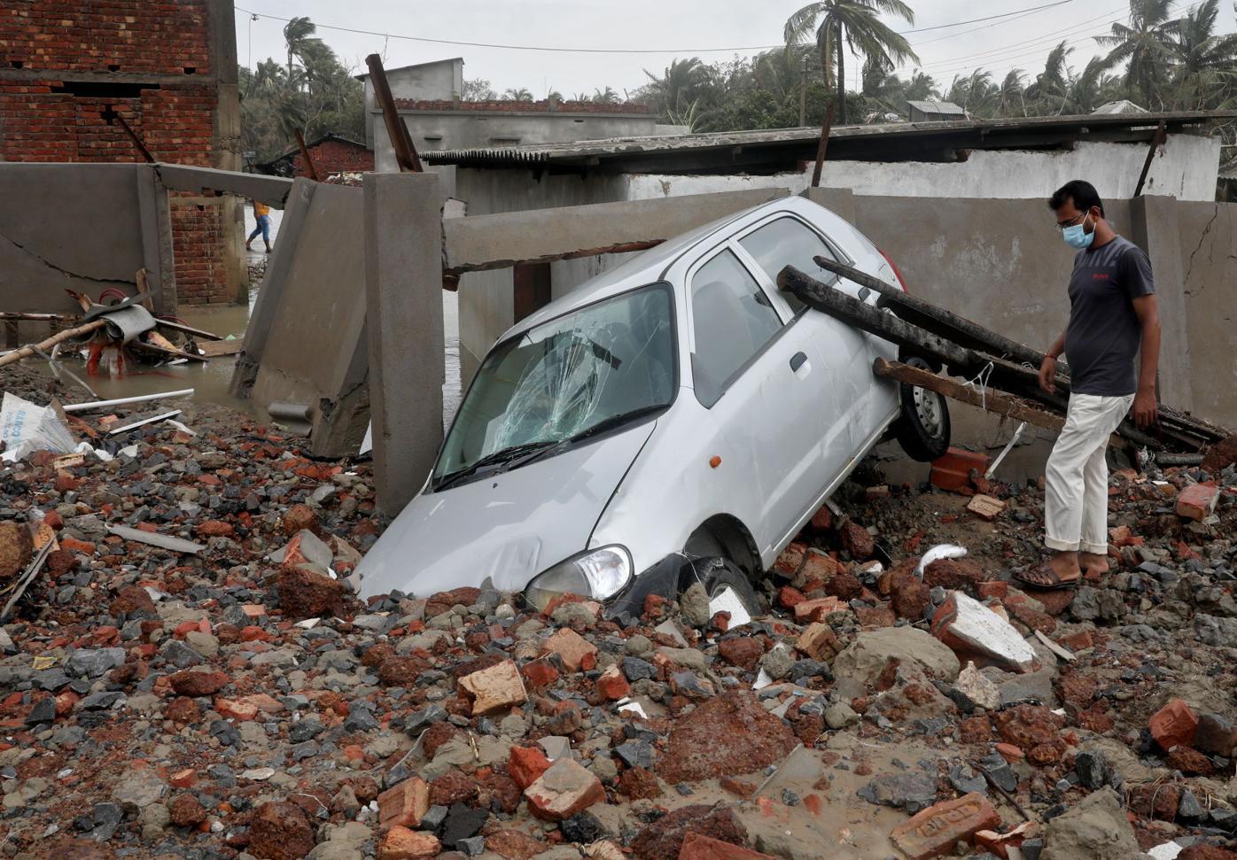 A man walks past a damaged car following Cyclone Yaas in Shankarpur
