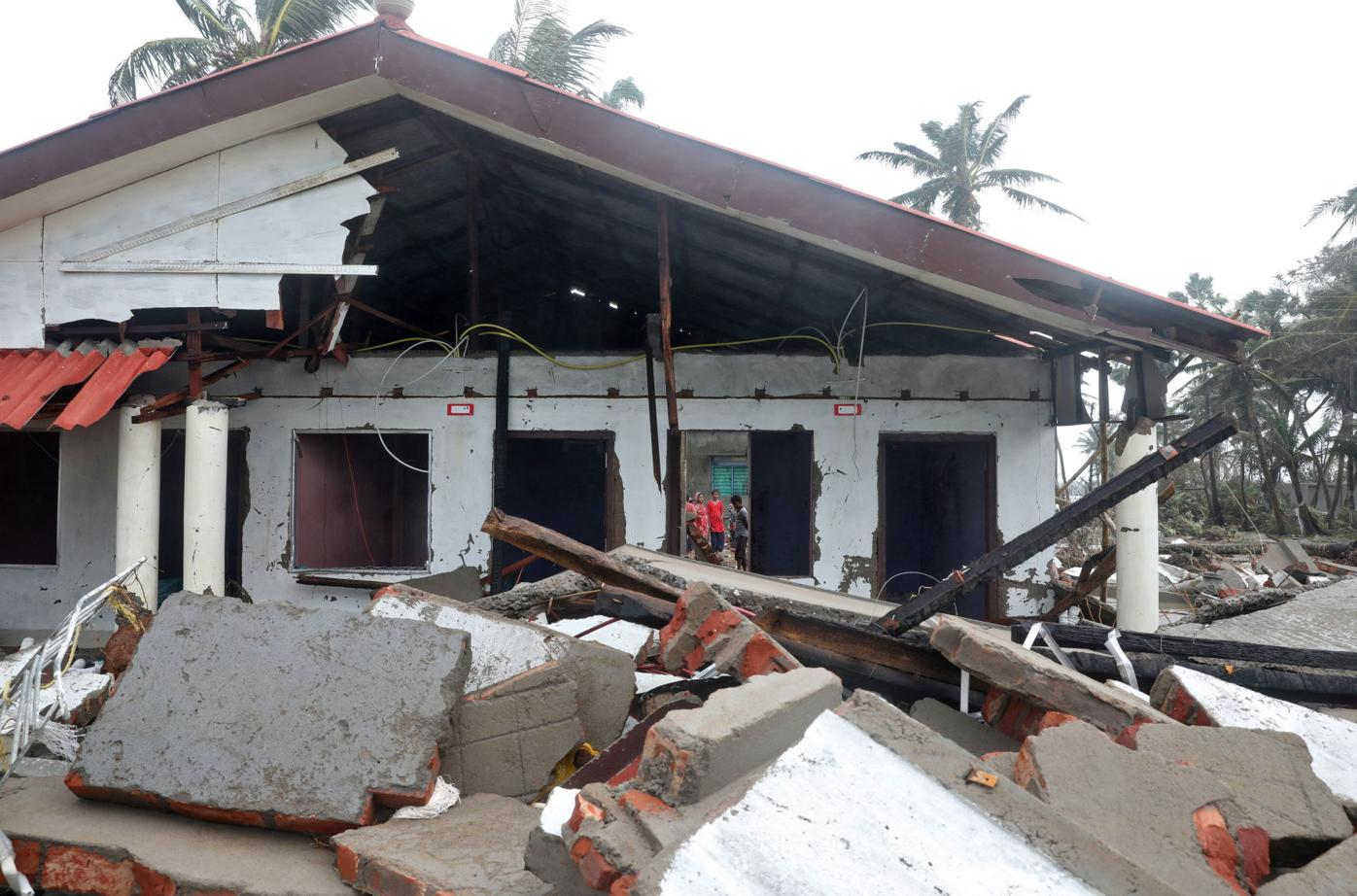 People stand near a damaged tourist lodge on a beach front following Cyclone Yaas in Shankarpur