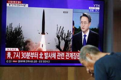 A man watches a TV showing a file picture for a news report on North Korea firing two unidentified projectiles