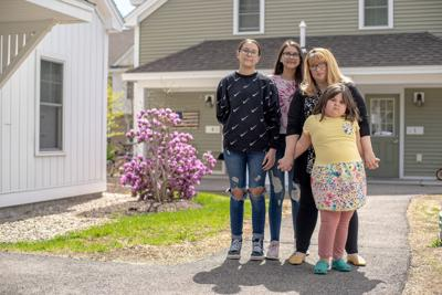 Carrie Duran stands with her three children