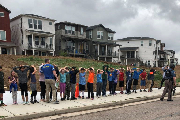 Schoolchildren stand in a line outside near the STEM School during a shooting incident in Highlands Ranch, Colorado, U.S. in this May 7, 2019 image obtained via social media