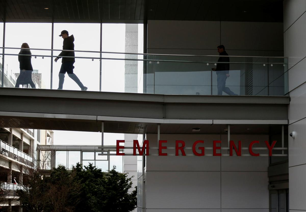 People walk on a skybridge from the emergency room building at Providence Regional Medical Center after coronavirus victim treated in Everett