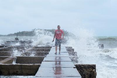 A man gets splashed by rough waves at a deck as Tropical Storm Karen approaches in Humacao