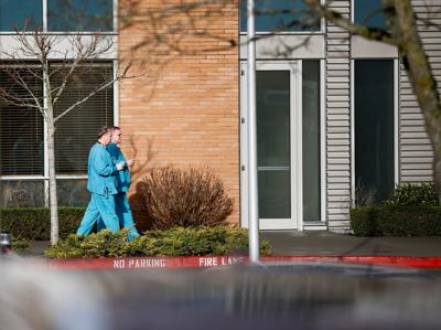 Employees in scrubs walk on the campus at Providence Regional Medical Center after coronavirus victim treated in Everett