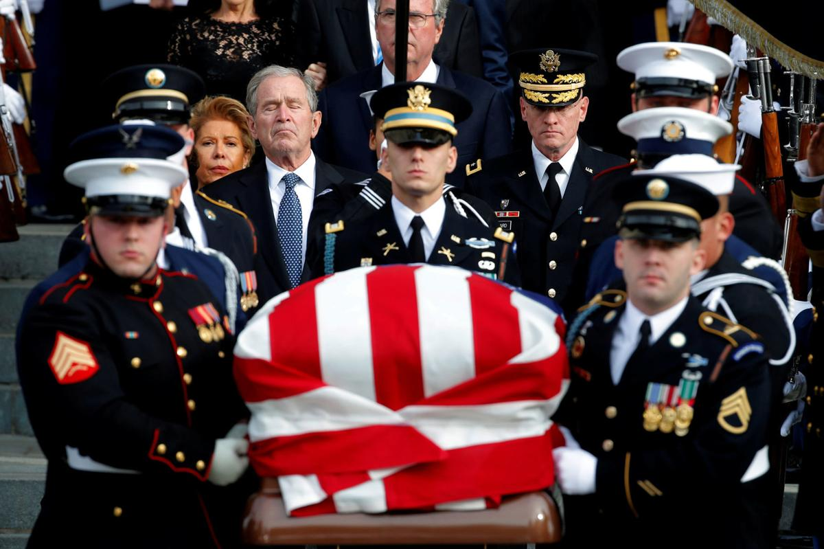 Former U.S. President George W. Bush follows military honor guard as they carry casket out of state funeral for his father former U.S. President George H.W. Bush at Washington National Cathedral
