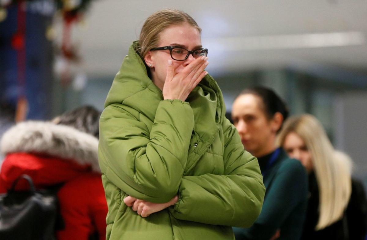 A woman reacts in front of a memorial for the flight crew members of the Ukraine International Airlines Boeing 737-800 plane that crashed in Iran, at the Boryspil International airport