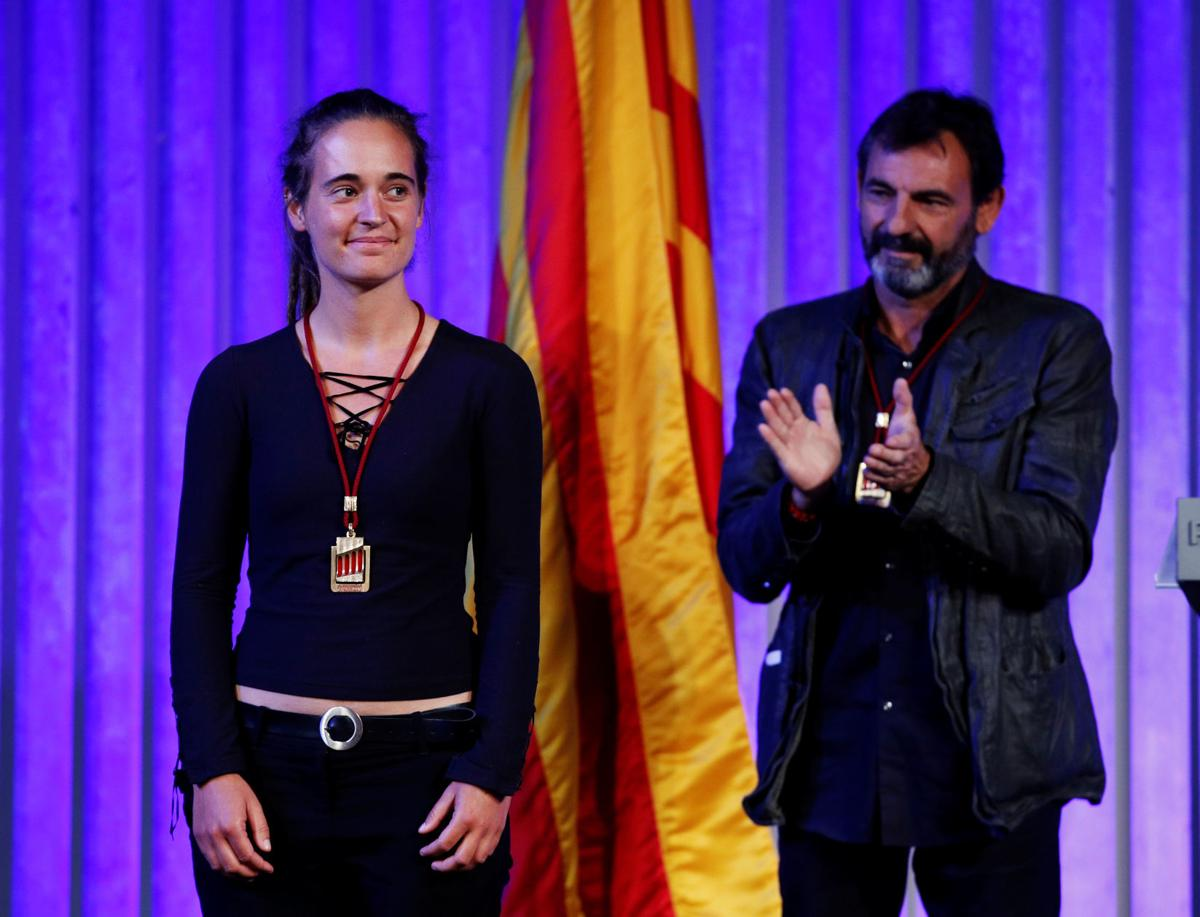 German captain of rescue ship Sea-Watch 3 Carola Rackete is applauded by director of Spanish NGO Proactiva Open Arms Oscar Camps, after they received the Catalan parliament award