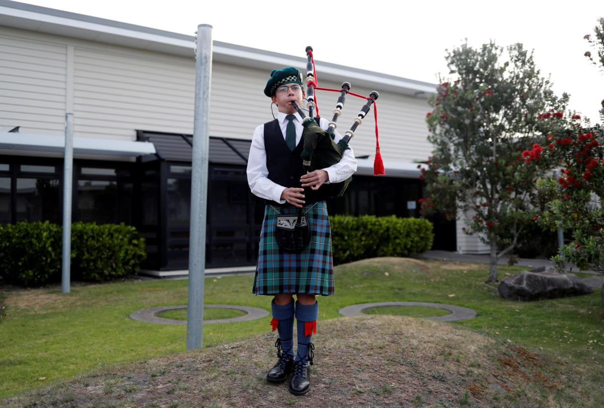 A boy plays bagpipes after a minute of silence for the victims of the White Island volcano eruption, at the hospital in Whakatane