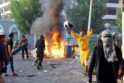 Iraqi demonstrators clash with Iraqi security forces during the ongoing anti-government protests in Baghdad
