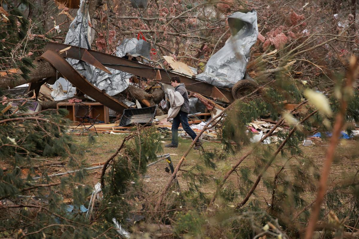 A man carries a sack through damage caused by a string of tornadoes that resulted in several fatalities in Beauregard
