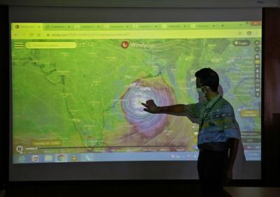 A scientist at India Meteorological Department Earth System Science Organisation, points to a section of the screen showing the position of the Cyclone Amphan to media people inside his office in Kolkata