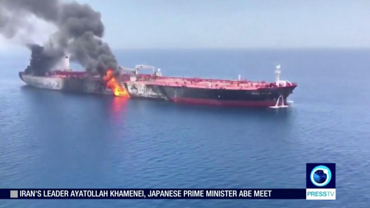 Still image taken from a video appears to show two tankers at sea, one of which has a large plume of dark smoke in the Gulf of Oman