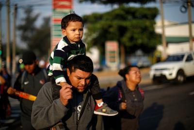 Father and son walk in a caravan of migrants en route to U.S. in San Salvador