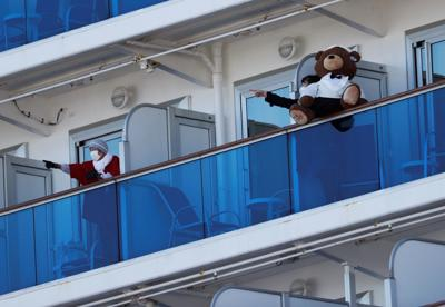 Passengers talk to each other on the balconies of their cabins on the cruise ship Diamond Princess, where dozens of passengers were tested positive for coronavirus, at Daikoku Pier Cruise Terminal in Yokohama