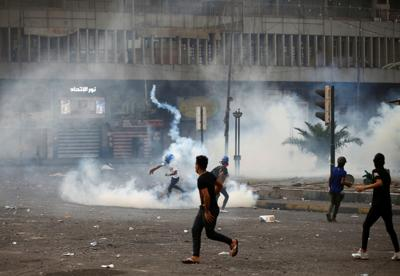 A demonstrator throws away a tear gas canister
