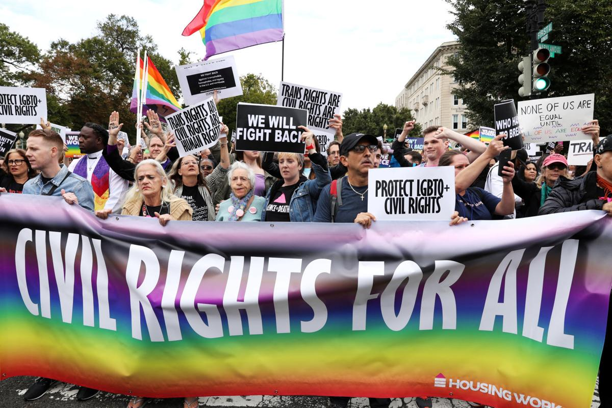 LGBTQ activists and supporters block the street outside the U.S. Supreme Court as it hears arguments in a major LGBT rights case in Washington