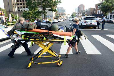 Paramedics roll a stretcher near the scene of a shooting incident in which several police were injured in Philadelphia