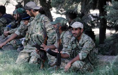 Turkey-backed Syrian rebel fighters sit together near the border town of Tel Abyad