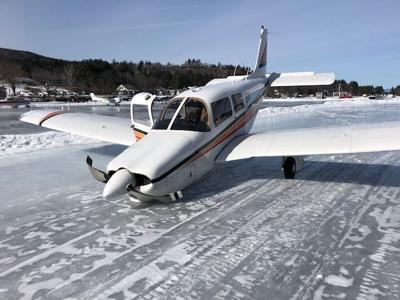 Single-engine plane skids off ice runway, strikes snowbank