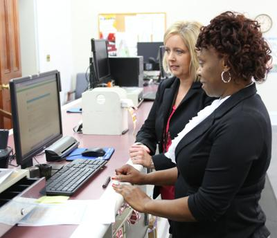 Left to right: Lisa Blankenship with Alabama Department of Revenue and Chief Clerk Elaine Tarver with the Bullock County Probate Judge's office reveiw the newly installed title software.
