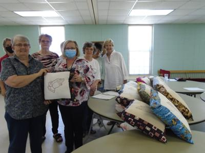 "At the April 12, 2021, meeting of the Women on Mission (WOM), Vicky Hall presented the ""Praying Hands"" embroidered pillows she made to Tracy Larkins, Director of the Bullock County Department of Human Resources (DHR). These will go into the homes of foster children in Bullock County who are sponsored by the DHR. (Photo by Faye Gaston)"