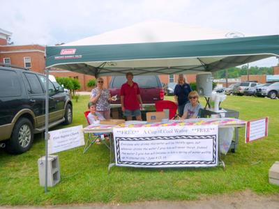 The WOM (Women on Mission) of First Baptist Church were hosts in a booth at the Chunnenuggee Fair on May 11, 2019. They were giving cups of cold water, tracts with Bible verses  in English and Spanish, Salvation bracelets, and Gospel coloring books with crayons. (Photo by Faye Gaston)