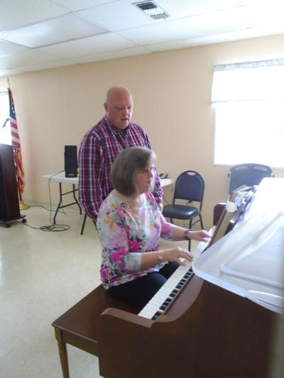 Pastor of Faith Baptist Church in Union Springs, Randal Atkins, and his wife Phyllis, led the singing of a hymn at the Union Springs Senior Citizens Nutrition Center on October 1, 2021, before he spoke to the senior citizens. (Photo by Faye Gaston)