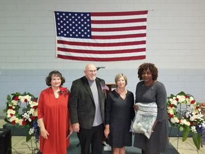 Posing with the two memorial wreaths were Faye Gaston who dedicated the wreaths, Committee Chairman Gene Nelson who presided over the program, Tourism Council President Heather Klinck who presented an afghan to the featured speaker CM SGT (R) Janice Patrick. (Photo by David Padgett)