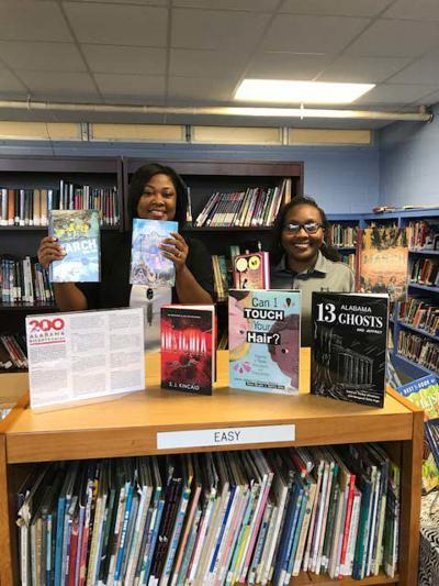 ACES Bullock County Coordinator, Carla Elston and South Highland Middle Librarian, Ardrinnia Bell, display books donated to the school's library by the University of Alabama Center for Economic Development (UACED), the University of Alabama School of Library and Information Studies and the Alabama Cooperative Extension System in celebration of Alabama's 200th bicentennial birthday.  The collection of books were written either about Alabama or by Alabama authors.