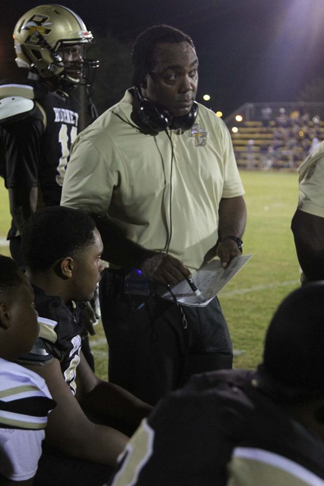 Coach J.R. Richardson talks to football players on sideline.