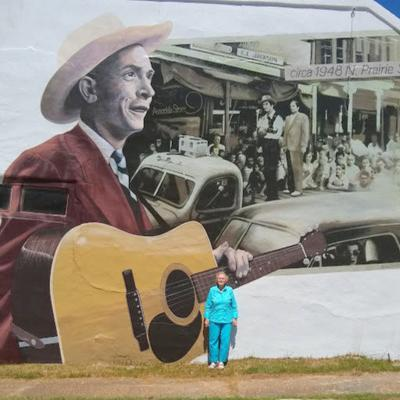 Mrs. Mary Ann Hendley stands in front of the new Hank Williams mural in downtown Union Springs.