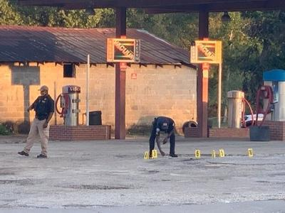 Sergeant S.D. Calhoun is shown placing evidence markers on the ground at the Robo car wash.
