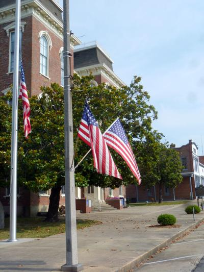 Every year United States flags fly in downtown Union Springs for the three-day holiday weekend for the annual Memorial Day, the last Monday in May. Memorial Day honors the men and women who have died while serving in the military. Government offices and many businesses are closed in Union Springs on that Monday. Photo shows flags flying at the Bullock County Courthouse where a historical monument stands to honor veterans of World War I. After World War I Memorial Day expanded to honor those military who died in all American wars from the beginning of our country. (Photo by Faye Gaston)